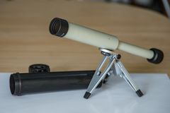 Spyglass on a small tabletop stand. Black plastic case with open lid. Selective focus close up stock image