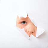 Spying. Cute little boy looking through paper hole stock images