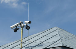 Spying cameras. Two cameras observing area from the roof royalty free stock photo