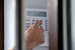 Spying a man arming a burglar alarm system Stock Images