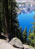 Spying Phantom Ship. Phantom Ship in Crater Lake seen through the trees on a sunny summer afternoon Royalty Free Stock Photo