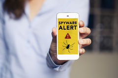 Spyware alert in a mobile phone held by hand. Virus alert in a smart phone screen royalty free stock photos