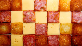 Sqare slices of salsmi, bread, cheese. Background Royalty Free Stock Images