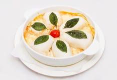 Sqiud farcito su un piatto bianco con le foglie verdi immagine stock