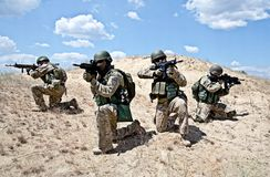 Squad in action. Squad of soldiers in the desert during the military operation Royalty Free Stock Image