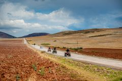 Squad of bikers are riding through valley in Peru. Squad of brave bikers are riding through sandy valley in Peru stock photo