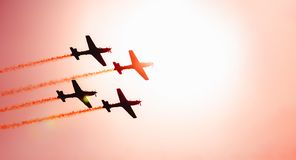 Squad of four airplanes flying together passing in front of the. Silhouette of a squad of four airplanes flying together leaving a smoke trail behind, passing in stock photos
