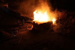 Squad of Four Firefighters Dousing a Burning Shed. A squad of four firefighters dousing a burning shed and wooden fence with fire hose. The fire takes place in Royalty Free Stock Photos