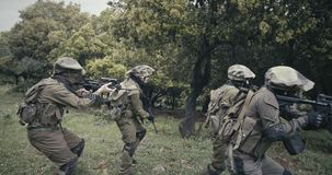 Squad of fully armed commando soldiers during combat in a forest scenery stock video