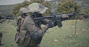 Squad of fully armed commando soldiers during combat in a forest scenery. Squad of fully armed soldiers during combat in a forest scenery stock footage