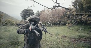 Squad of fully armed commando soldiers during combat in a forest scenery stock video footage