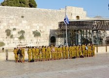 A squad of Israeli soldiers on the square near the Western Wall (Jerusalem). A squad of Israeli soldiers on the square near the Western Wall under national flag Stock Photography