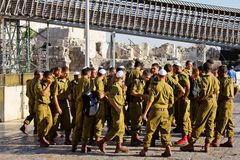 A squad of Israeli soldiers on the square near the Western Wall (Jerusalem). A squad of Israeli soldiers on the square near the Western Wall under national flag Stock Images