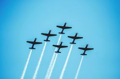 Squad of six airplanes flying together leaving a smoke trail beh. Ind going up on the sky. Aerial acrobatics airplanes. Clear blue sky day royalty free stock photography