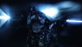 Attacking under cover of darkness. Squad of soldiers attacking in action under cover of darkness back light Royalty Free Stock Photo
