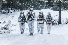 Squad of soldiers in winter forest. Winter arctic mountains warfare. Action in cold conditions. Squad of soldiers with weapons in forest somewhere above the Royalty Free Stock Photos