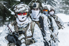 Squad of soldiers in winter forest. Winter arctic mountains warfare. Action in cold conditions. Squad of soldiers with weapons in forest somewhere above the Royalty Free Stock Photo