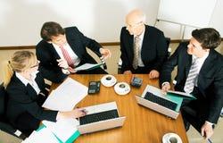 Squadra di affari che discute le varie proposte Immagini Stock Libere da Diritti