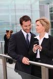 Squadra di affari che guarda telefono mobile esterno Fotografie Stock