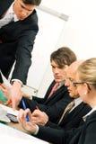 Squadra di affari che ha discussione in ufficio Fotografia Stock