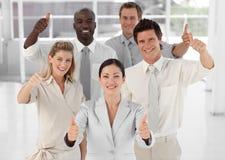 Squadra di affari che sorride sostenendo i pollici Immagine Stock