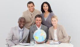 Squadra di affari che tiene un globo terrestre Immagini Stock
