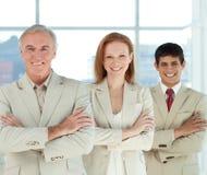 Squadra di affari con le braccia piegate in una riga Immagine Stock