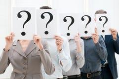 Squadra di affari dietro i punti interrogativi Fotografia Stock Libera da Diritti