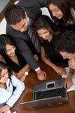 Squadra di affari in un computer portatile dell'ufficio Immagine Stock