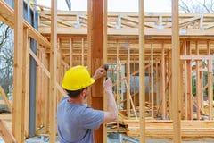 Squadra di costruzione che lavora al rivestimento di un nuovo, due storia, costruzione del tetto di appartamento commerciale nell immagine stock libera da diritti