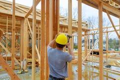 Squadra di costruzione che lavora al rivestimento di un nuovo, due storia, costruzione del tetto di appartamento commerciale nell fotografie stock libere da diritti