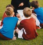 Squadra di football americano dei bambini con l'allenatore al campo di calcio Bordo di Explaining The Tactics della vettura della immagini stock libere da diritti