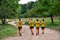 Squadra di partecipanti della corsa del fango sul corso Fotografia Stock