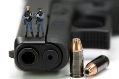 Squadra di SCHIAFFO miniatura che si leva in piedi su una pistola. Fotografia Stock Libera da Diritti
