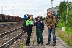 Squadra di viaggiatori con zaino e sacco a pelo che attendono un treno Fotografia Stock