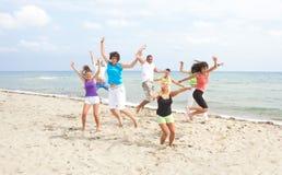 Squadra felice che salta sulla spiaggia immagine stock