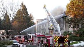 Squadre del pompiere che combattono il fuoco del complesso condominiale video d archivio