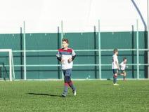 Squadre di football americano - i ragazzi in abiti sportivi rossi, blu, bianchi giocano a calcio sul campo verde ragazzi che gocc immagine stock