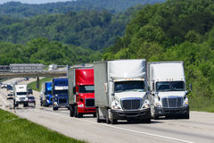 A squadron of eighteen-wheelers lead the way down an interstate highway in eastern Tennessee. Heat waves rising from the pavement give a shimmering effect to Royalty Free Stock Images