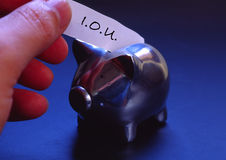 Squandered Savings. A hand putting an IOU slip into a piggyt bank royalty free stock photography