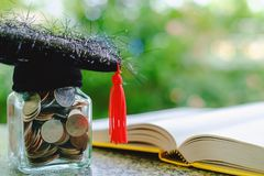 Square academic cap with the glass jar of coin and opened book o. N blurred natural green background for education, finance and saving money concept Royalty Free Stock Photo