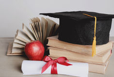 Square academic hat. Graduation. Square academic hat with books Stock Photos