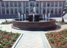 Square in Arandjelovac, Serbia. On sunny day with blue sky and fountain and historic building behind the fountain royalty free stock images