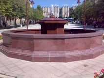 Square in Arandjelovac, Serbia. On sunny day with blue sky and non working fountain in foreground and historic building behind the fountain royalty free stock photos