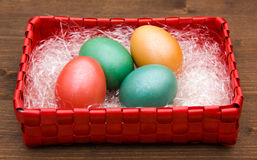 Square basket with colored eggs on wood Royalty Free Stock Images