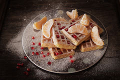 Square Belgian waffles with a tangerine pomegranate. Square Belgian waffles with a tangerine and pomegranate and sprinkle with powdered sugar stock image