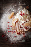 Square Belgian waffles with a tangerine pomegranate. Square Belgian waffles with a tangerine and pomegranate and sprinkle with powdered sugar royalty free stock images