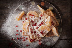 Square Belgian waffles with a tangerine pomegranate. Square Belgian waffles with a tangerine and pomegranate and sprinkle with powdered sugar stock images