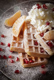 Square Belgian waffles with a tangerine pomegranate. Square Belgian waffles with a tangerine and pomegranate and sprinkle with powdered sugar royalty free stock image