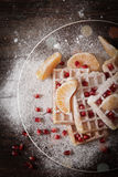 Square Belgian waffles with a tangerine pomegranate. Square Belgian waffles with a tangerine and pomegranate and sprinkle with powdered sugar royalty free stock photography